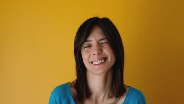 Young woman looking at the camera smiling and winking on yellow background