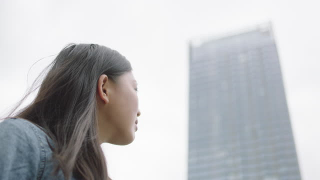 young woman looking at the skyscraper - looking up stock videos & royalty-free footage