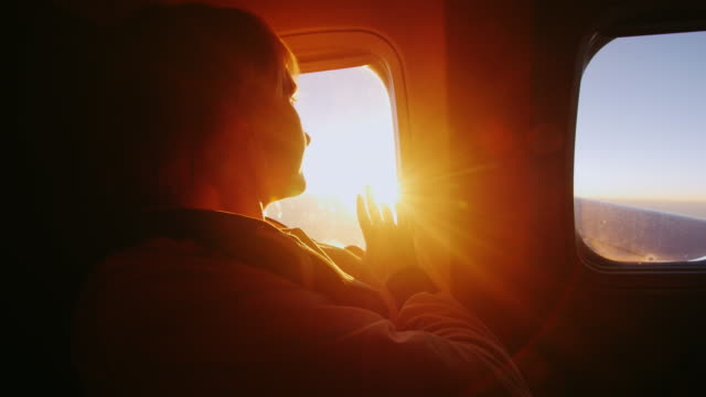 young woman looking at the sun from the window of an airliner. it touches the rays of the sun. concept - touch the dream, the perfect trip and vacation - dream video stock e b–roll