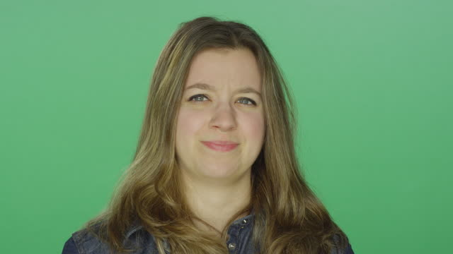 Young woman looking disgusted and annoyed, on a green screen studio background Young woman looking disgusted and annoyed, on a green screen studio background disgust stock videos & royalty-free footage
