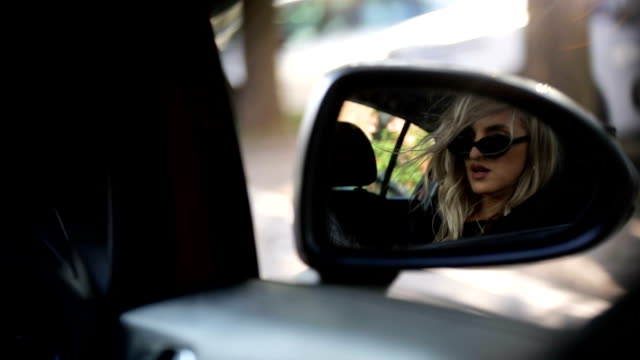 Young woman looking in the car mirror Young woman looking in the car mirror rear view mirror stock videos & royalty-free footage