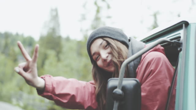 Young woman looking into car mirror and making funny faces.