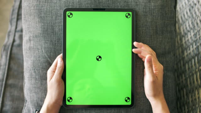 Young woman Looking on digital tablet with a green screen