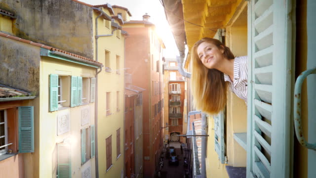 A young woman looking out of the window to a medieval street smiling and waving her hand A young woman looking out of the window to a medieval street smiling and waving her hand. Nice, France. Apartments and villas for rent. Vacation Europe Travel Tourism house rental stock videos & royalty-free footage