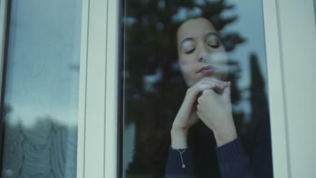Young woman looking outside through the window