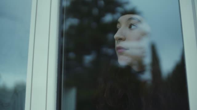 junge frau schaut durch das fenster nach draußen - introspektion stock-videos und b-roll-filmmaterial