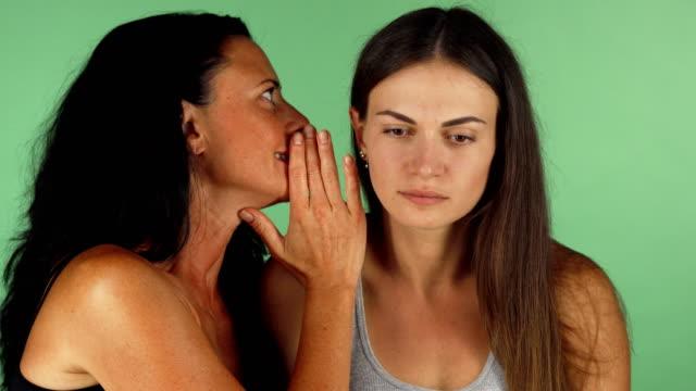 junge frau, während ihre freunde ihr flüstern schockiert - kosmetik beratung stock-videos und b-roll-filmmaterial