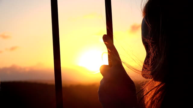 young woman looking the sunset behind the railing video