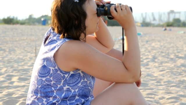 Young woman looking through binoculars on beach video
