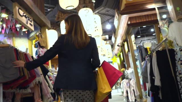 ung kvinna tittar genom kläder - spendera pengar bildbanksvideor och videomaterial från bakom kulisserna