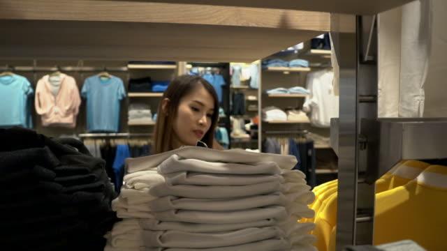服を探している若い女性 - 小売販売員点の映像素材/bロール