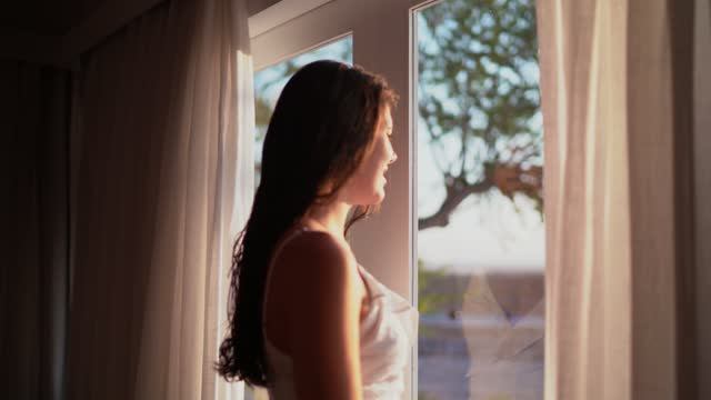 Young woman looking through hotel window