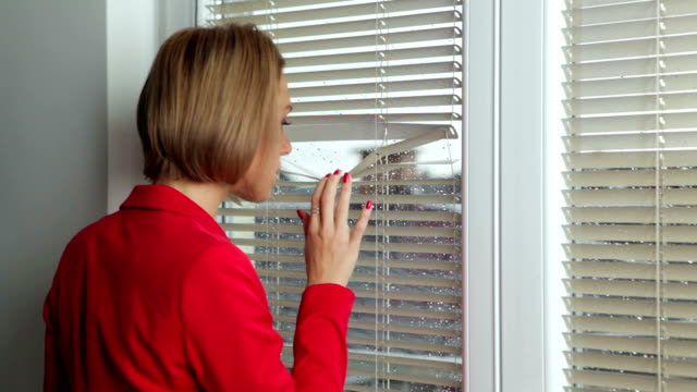 Young woman looking through the window at home video
