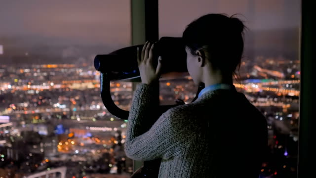 Young woman looking through tourist telescope and exploring night cityscape