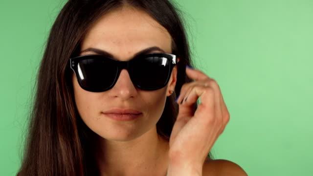 junge frau, die an der kamera über ihre sonnenbrille - sonnenbrille stock-videos und b-roll-filmmaterial
