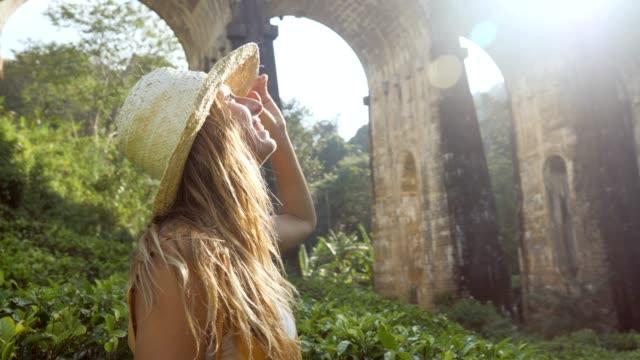 stockvideo's en b-roll-footage met jonge vrouw die omhoog oude treinbrug bij zonsondergang in sri lanka bekijkt die het mooie landschap van de heuvel en theeplantage overweegt. het reisavontuur van mensen in het concept van azië - camelia white