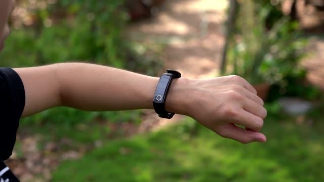 Una mujer joven mira la pantalla vacía en el reloj de la banda deportiva. - vídeo