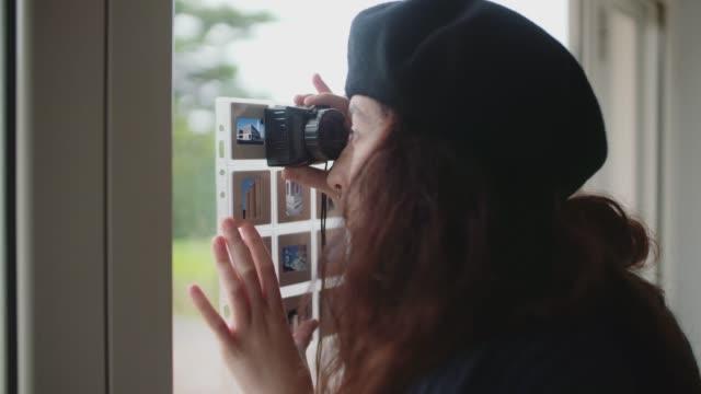 ung kvinna tittar på fotografiska diabilder nära fönstret - diabild bildbanksvideor och videomaterial från bakom kulisserna
