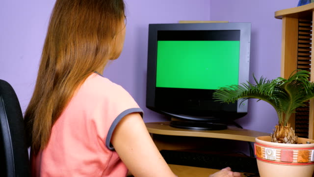 A young woman looks into the monitor, rejoices and claps her hands.