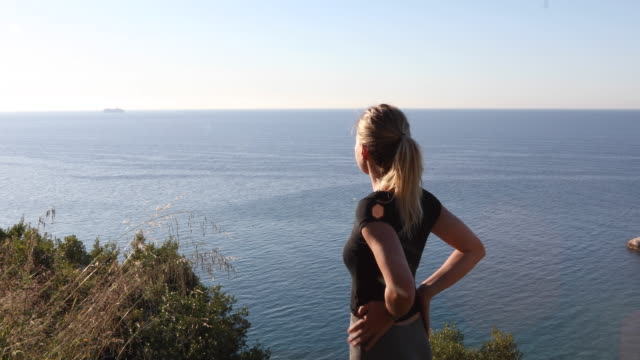 young woman looks off from coastal slope at sunrise - mani sui fianchi video stock e b–roll
