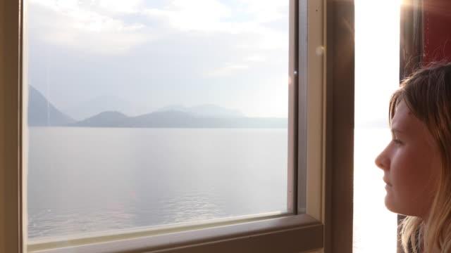 vídeos de stock e filmes b-roll de young woman looks out of window to lake at sunrise - lago maggiore