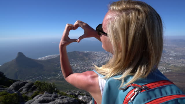 Young woman loving Cape Town Young woman makes heart shape with fingers on top of Cape Town famous Table Mountain. table mountain national park stock videos & royalty-free footage