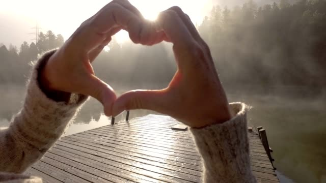 Young woman loving nature, standing on lake pier making a heart shape finger frame video