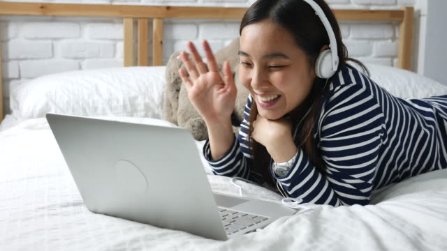 Young woman lying bed in a video call on laptop computer with headphone, Video Conference video
