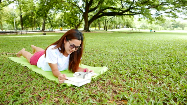 Young Woman Lying Down and Reading a Book in Park video