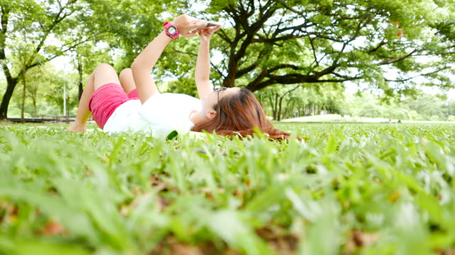 Young Woman Lying Down and Using Smartphone in the Park video