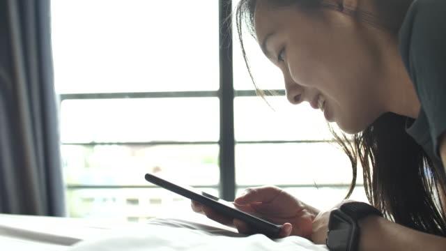 スマートフォンを使って横たわっている若い女性 - オンラインショッピング点の映像素材/bロール