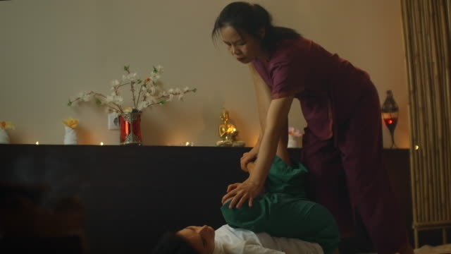 young woman lying down while enjoying the acupressure techniques of traditional thai massage at luxury spa and wellness center. - cultura tailandese video stock e b–roll