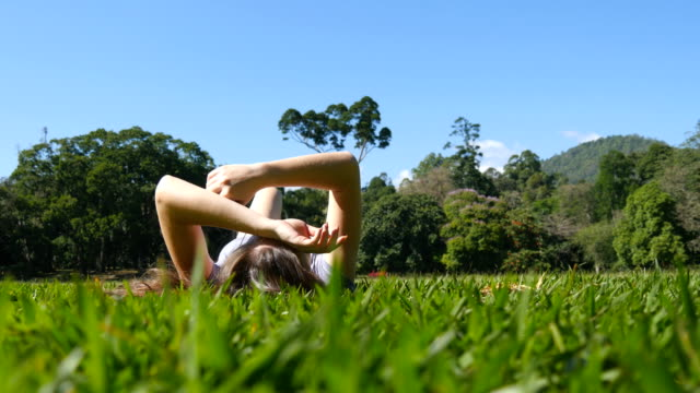 Young woman lying on green grass in park and relaxing. Girl sitting on meadow at nature and watching at the sky. Female looking at the landscape and enjoying vacation. Low angle of view Rear Back view video