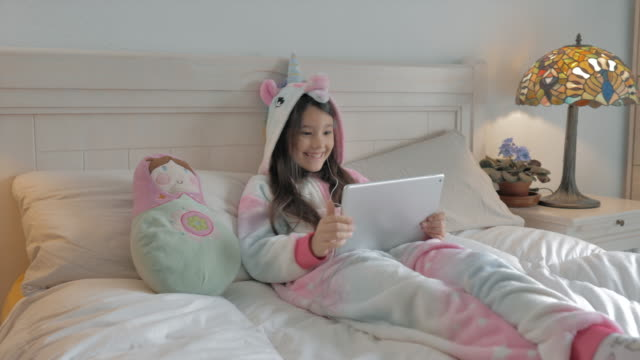 young woman lying on the bed and in unicorn hood pyjamas calls happy by group video with tablet