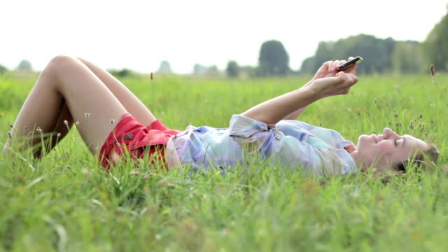 vidéos et rushes de jeune femme allongée sur l'herbe et l'envoi de sms - allongé sur le dos