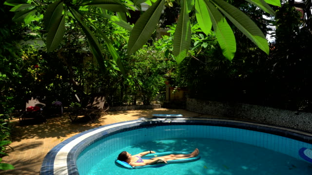 Young woman lying on water mattress in the pool on a sunny day video