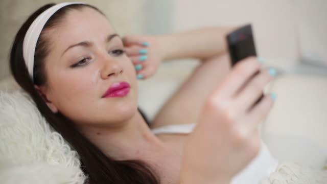 молодая женщина, лежа с мобильного телефона - аксессуар для волос стоковые видео и кадры b-roll