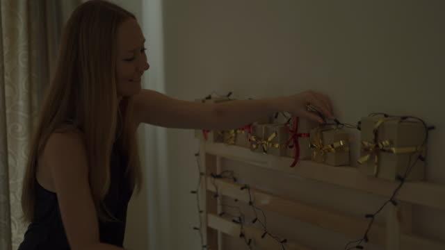 eine junge frau macht einen adventskalender für ihre kinder - adventskalender stock-videos und b-roll-filmmaterial