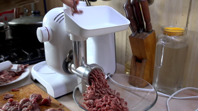 A young woman makes ground meat using a meat grinder in her kitchen video