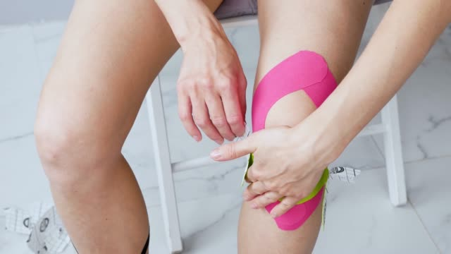 young woman makes herself taping a knee post-rehab-sitting