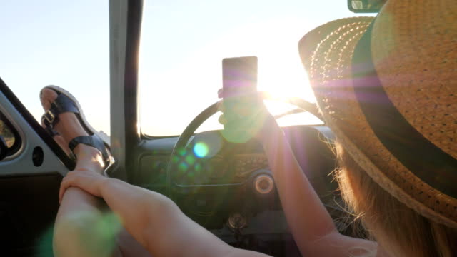 young woman makes pictures on phone sitting in auto, beautiful girl makes selfie photo on mobile in vintage car video