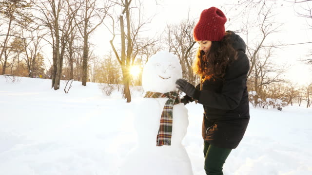 Young woman making a snowman. Young woman making a snowman at sunset. She is in the park having fun and enjoying the beautiful winter time. snowman stock videos & royalty-free footage