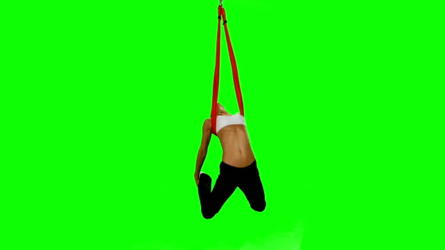 Young woman making antigravity yoga exercises with red hammock on video