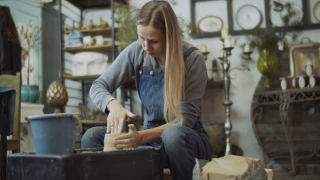 vídeos de stock, filmes e b-roll de mulher nova que faz a cerâmica em sua oficina da cerâmica, conceito da empresa de pequeno porte - cerâmica artesanato