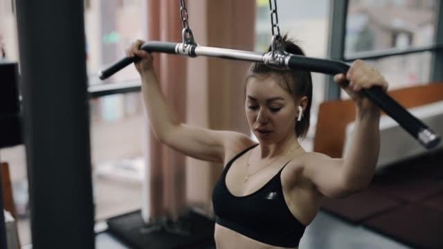 vídeos de stock, filmes e b-roll de mulher nova que faz o exercício no instrumento de treinamento na ginástica - comodidades para lazer