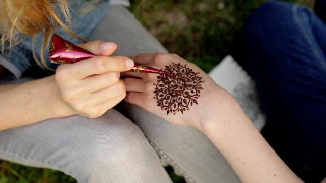 Young woman making floral mehendi on a hand using henna. Young woman making floral mehendi on a hand with henna. Process of applying mehendi on the female hand outdoors sitting on a grass in the evening. Close up shot. sari stock videos & royalty-free footage