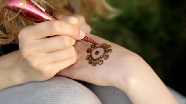 Young woman making floral mehendi on a hand using henna. video