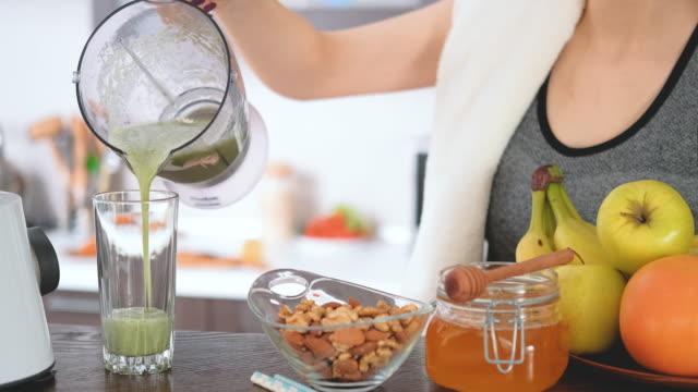 若い女性は家庭の台所でジュース マシンでトレーニングの後青汁を作るします。 - アプリコット点の映像素材/bロール