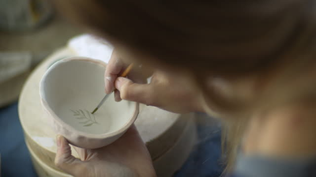 Young woman making handmade ceramics in her pottery workshop, small business concept