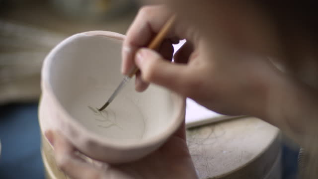 vidéos et rushes de jeune femme faisant la céramique faite à la main dans son atelier de poterie, concept de petite entreprise - pots de bureau